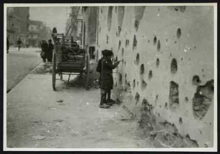 Deux enfants constatant les éclats d'obus sur un mur après un bombardement à Saint-Nazaire.